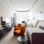 unique interior design with futuristic accent and purple sofa and unique orange chair and area rug and textured wall
