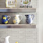 unique kitchen design with stainless steel floating shelf idea on brick wall with pottery decoration