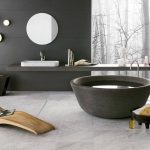 unique modern bath design with round bathtub and wooden reclining chair and floating gray vanity and gray painted wall