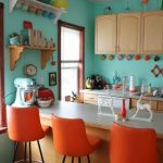vintage kitchen design with blue painted wall and orange stools and white dining table with wall racks and tan cabinetry