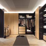 vintage oriental walk in closet in master bedroom with beige and black colors combination with runner rug on wooden floor with mannequin