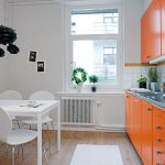 white mood kitchen design with glass window and orange cabinet and indoor plant and white breakfast nook and wall decoration