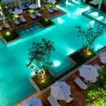 wonderful turquoise tone from luxurious swimming pool design with unique shape with concrete patio deck with umbrella patio