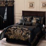 A fancy bedroom with black bed comforter set which has gold schemed pattern a wood bed frame with headboard