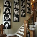 A lot of black and white canvas photo collage series along the wall  near the stairway