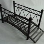 A metal bridge for garden with curved surface and handrails