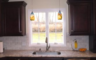 A pair of decorative pendant lamps over the kitchen sink white marble kitchen countertop dark finished wood wall cabinets