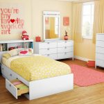 Bedroom interior design for toddler or kid consisting of white bed with shelf on headboard and under storage pink shag rug white storage system white bedroom vanity white bedside table