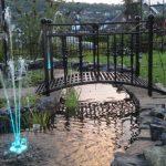 Black finished metal garden bridge idea over small artificial stream