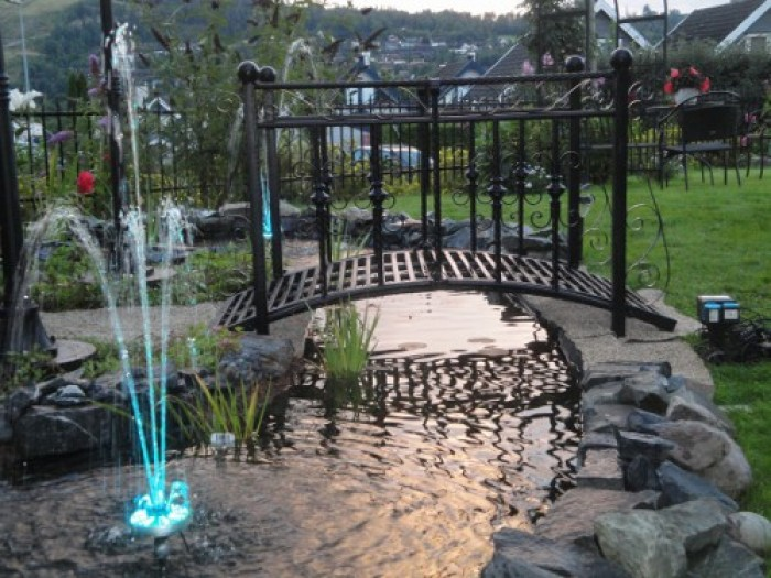 Lovely Black Finished Metal Garden Bridge Idea Over Small Artificial Stream