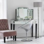 Clear acrylic makeup vanity chair with chrome base modern bedroom vanity with three units of vanity mirrors in different sizes a corner chair in grey high base floor lamp with grey lampshade