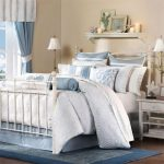 Country beach style bedroom decor idea with white metal bed frame plus built in metal rail shaped headboard and footboard a pair of white bedside tables a white shelf over bed  blue