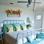 Country style bedroom idea with beach theme blue stained metal bed frame with headboard and footboard white bed comforter with gold framed blue pillow cases round top bedside table in blue