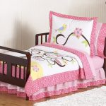 Dark brown wood bed frame in full size for toddler with floral and animal bed comforter set in white and pink