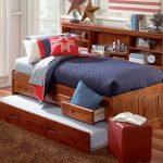 Full bed daybed made of wooden with additional trundle and shelving unit a small red ottoman side table