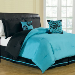 Full sized bed frame with black leather headboard and reversable black and turquoise bed comforter black finished wood bedside table idea with table lamp