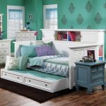 Full sized white wooden daybed with built in shelving unit and extra trundle blue painted side table with drawers