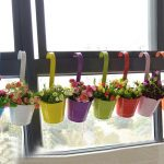 Glossy and colorful pots hooked at the windows with beautiful flowers