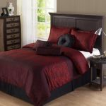 Maroon Bed Comforter Set In King Size Dark Finished Bed Frame With Headboard Simple And Small Dark Finished Bedside Table With Modern Metal Table Lamp Tall Storage System