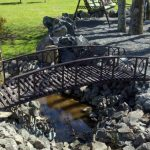 Metal bridge for garden with lower handrail system