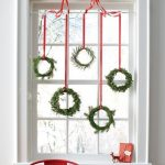 Mini green wreaths hung at the window for Christmas