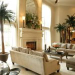 Natural And Elegant Living Room With Big Plants White Fireplace And Sofas Plus Ottoman For Home Furnishing Catalogs