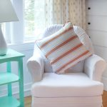 Pretty turquoise nursery side table with elegant white table lamp with white lampshade pure white nursery chair with orange stripes motif accent pillow