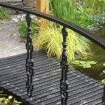 Simple garden bridge made of metal which is stained in black and only has one side of handrail system