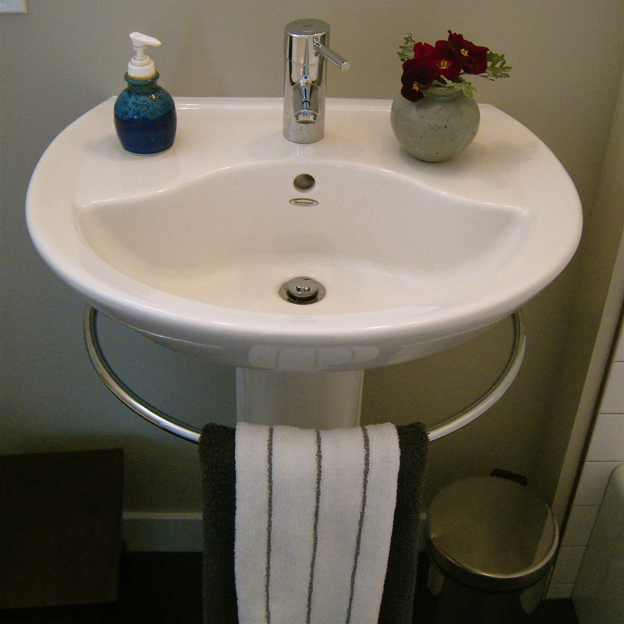 small white pedestal sink with towel bar