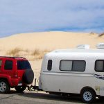 White Small Travel Trailer Manufacturers With Red Car At Desert