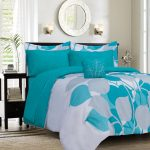 White and turquoise bed comforter set with floral motif round framed mirror over the bed frame a pair of decorative wall light fixtures black finished wood bedside table
