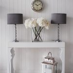 White antique lacquer console table idea a pair of table lamp with dark grey lampshades an antique wall clock clear glass vase with white flowers
