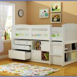 White toddler sized bed frame with side rail headboard footboard under bookshelves and drawer system cute bedroom rug for kids