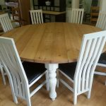 Wooden 8 Person Round Dining Table With White Bases And White Chairs