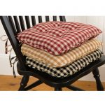 a pile of country styled chair pads in three color options
