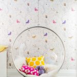 clear acrylic made hanging chair with colorful accent pillows