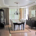 short curtain rods made of metal floor to ceiling window curtains in brown white window blinds an armoire with glass door a vintage storage in black finishing a square mirror with frame a dining set