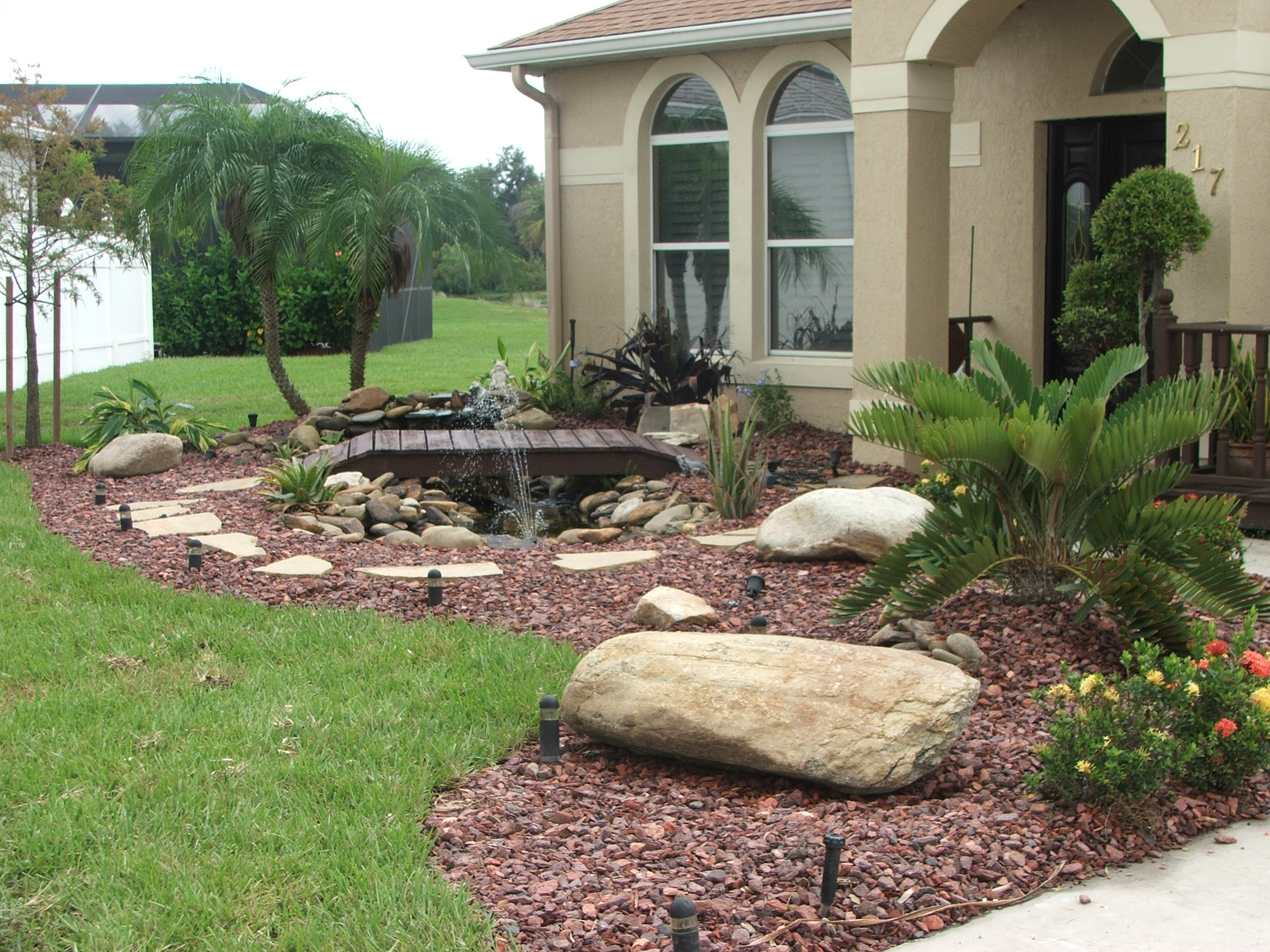 Landscaping rocks pool landscaping with river rocks for Front garden landscaping