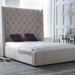 Large Tall Upholstered Bed With Purple Pillows And Classic Table