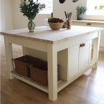 Lovely Wooden White Stand Alone Kitchen Islands With Baskets Flower Vase Plus Fruit On Top