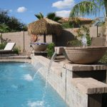 Stylish Water Fountain With Stone Design And White Outdoor Chairs
