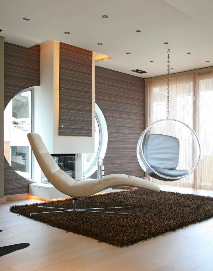 of chairs that hang from the ceiling with sleeper chair and fur rug