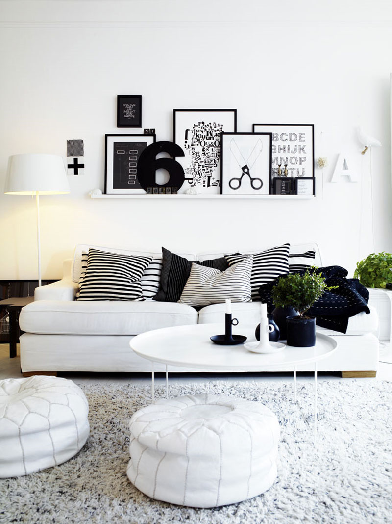 White And Black Theme Living Room With Wall Accessories White Sofa Stripes  Pillows Standing Lamp Table