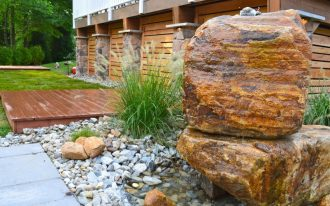 Wooden Backyard Deck With Large Rocks For Landscaping
