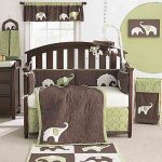 A nursery room decor theme with full of elephant pictures dark brown finished baby crib