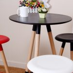 A tall bar table with round black tabletop