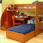 A twin size bunk bed over another twin size bunk bed with computer desk and stairs