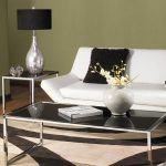 Avenue six couch in white with fluffy black throw pillows modern side table with black lampshade table lamp a center table with black glass tabletop