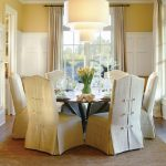 Baroque Chair With White Slipcovered Dining Chairs Round Dining Table And Big Chandelier