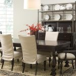 Black Wooden Furniture With White Slipcovered Dining Chairs And Patterned Rug